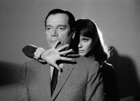 "1965, France --- American actor Eddie Constantine and Danish actress and singer Anna Karina on the set of ""Alphaville, Une Etrange Aventure de Lemmy Caution"" (Alphaville, a Strange Adventure of Lemmy Caution) by her husband French Swiss director, screenwriter and producer Jean-Luc Godard. --- Image by © Georges Pierre/Sygma/Corbis"